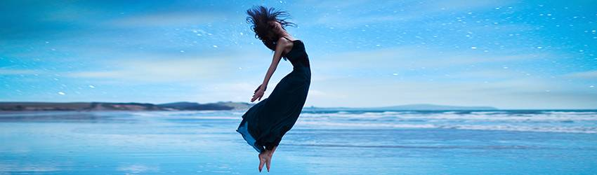 A shadowy woman is floating above the ocean with her hair flying in the wind.