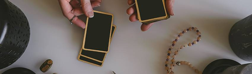 Black tarot cards with a gold trim.