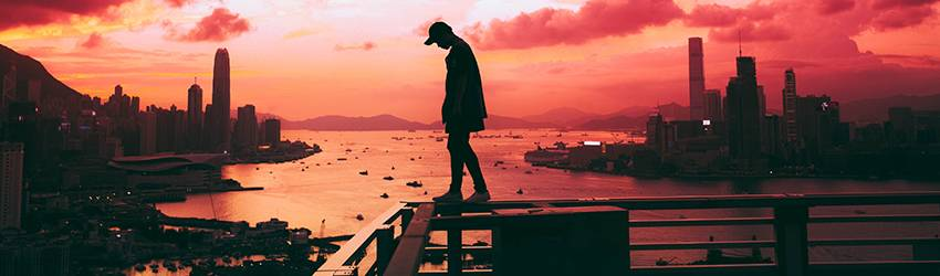 A person is watching a red sunset in front of a city skyline.