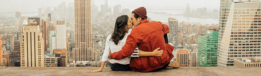 Two lovers kiss in front of the New York City skyline.