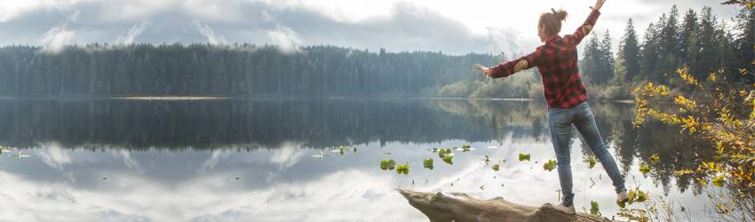 A person wearing a flannel and hunting boots balancing on a log over a lake in autumn time.