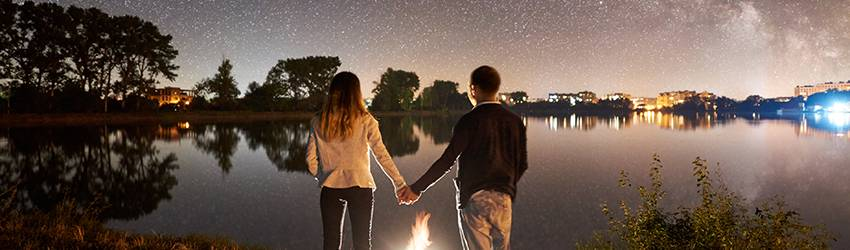 A couple holds hands above a fire while looking out on a lake.