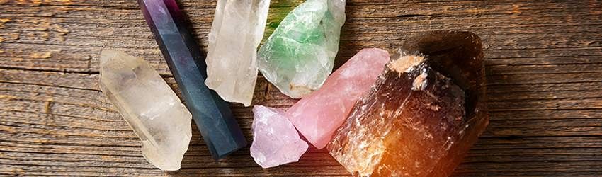 5 crystals sitting on a wooden table.