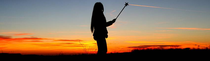Woman using a healing wand in front of a sunset.