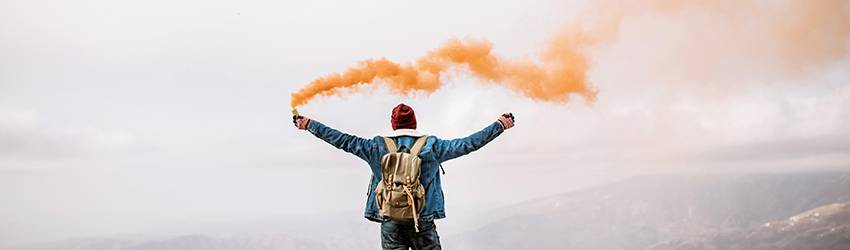 A person stands on top of a mountain holding an orange smoke spray.