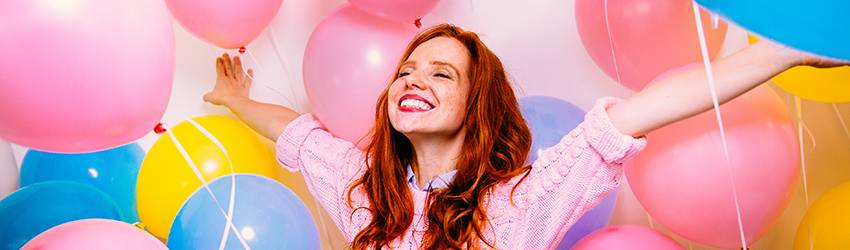 A Gemini woman smiles while surrounded by balloons.