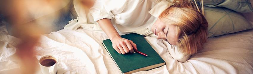 A person lays in bed which journaling about their dreams