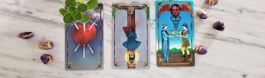 Three Tarot cards from the Astrology Answers Master Tarot Deck: The Hanged Man, 3 of Swords, and 2 of Cups. These represent the themes of July 2020 in this Tarotscope reading.