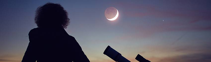 A person standing in front of a telescope, looking at the New Moon in Aquarius.