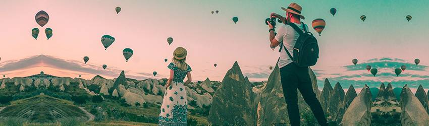 Two people stand in front of hot air balloons.