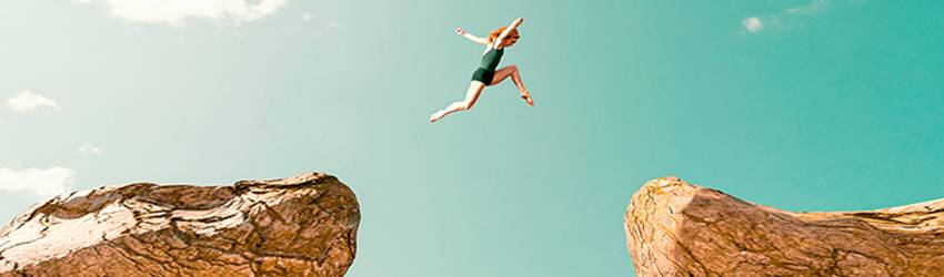 A woman jumps between cliffs representing her facing her fears during Mars Square Pluto.