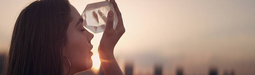Woman stands in front of a sunset and places a large clear quartz crystal to her forehead.