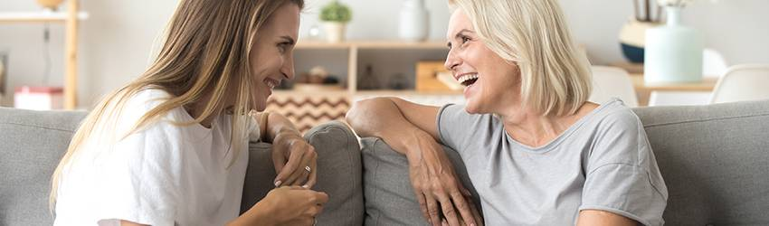 Two women sitting on a white couch chatting with each other.
