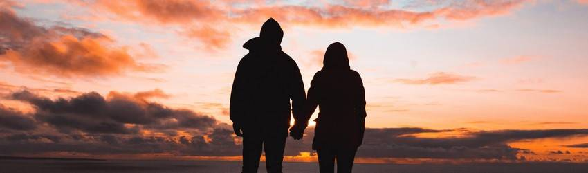A silhouetted couple holds hands while watching the orange and purple sunset.