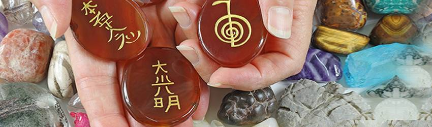 Reiki stones in someone's hands above crystals.