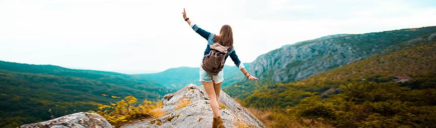 A woman is hiking on top of a mountain during Virgo season, she is facing away from the viewer and wearing navy and green hiking gear. Her arms are out like she is pretending to be an airplane.