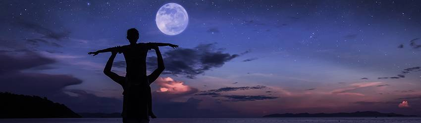 Man holding child above his head in front of the moon.