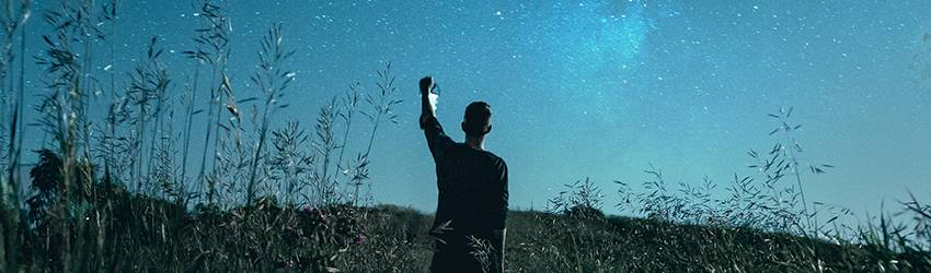 A silhouette of a man on a starry blue background.