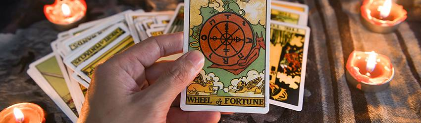 A person holding the wheel of fortune card up.
