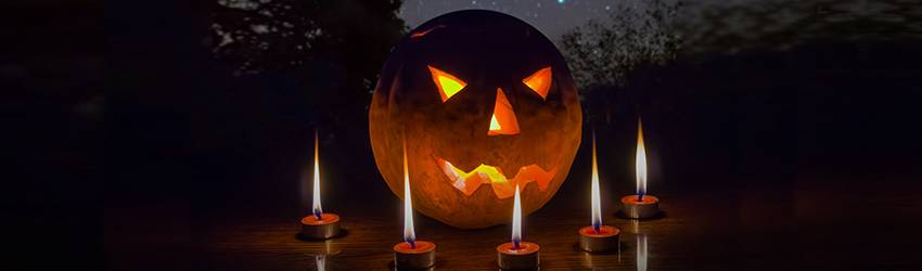 A carved pumpkin is surrounded by candles under a star filled sky on Halloween.