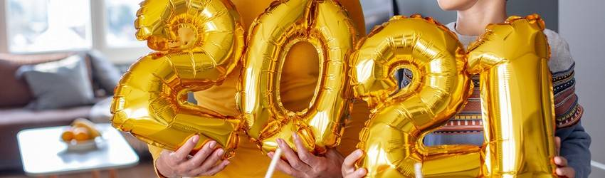 A mother and son hold gold foil balloons that spell out 2021.