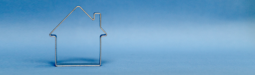 A metal cookie cutter house on a blue background.