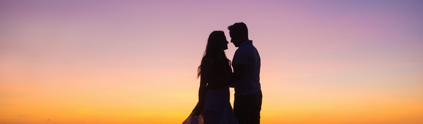 Two people stand under a sunset about to kiss.