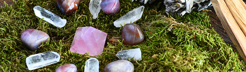 12 purple, white, and black crystals sit on some moss next to a candle.
