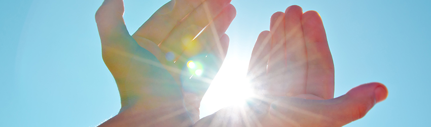 A person holds their hands up to the sky allowing the sun to peak through. This represents the power movement associated with Reiki healing.