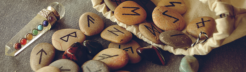 Runes on a table with a crystal wand.