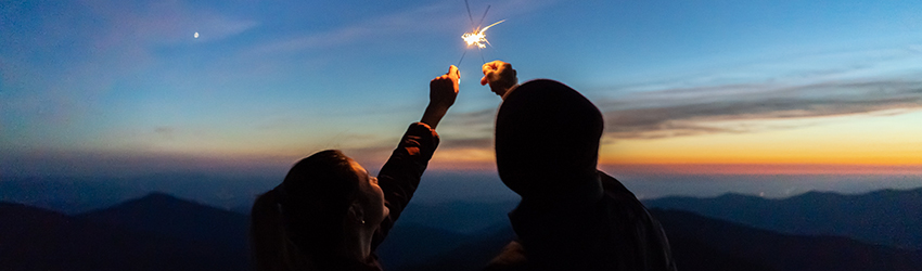 Two people put their sparklers together to create a bigger fire. The are silhouetted by a red and blue sunset in front of them.