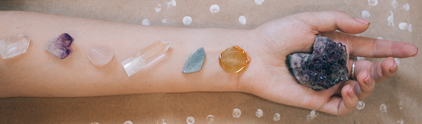 An arm lays on a wooden table with 7 different crystals all along it.