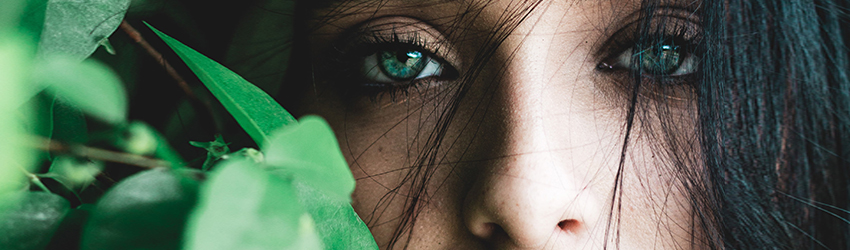 A close up of a black haired woman hiding behind some leaves.