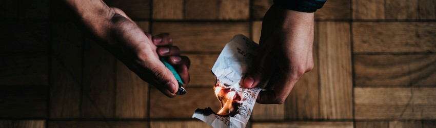 A man burns a piece of paper with a lighter to release the negative energy.