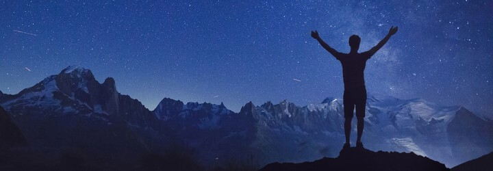A person standing on a mountain surrounded by the stars.
