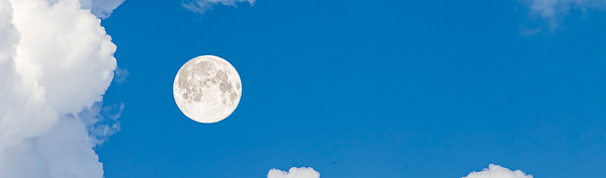 A Full Moon rests within a daytime blue sky surrounded by puffy clouds.