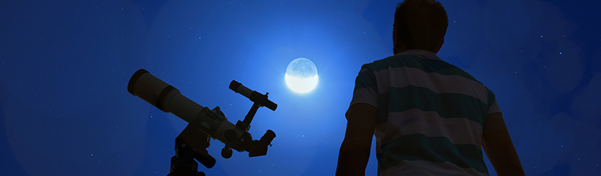 A man looking up at a Lunar eclipse with a telescope.