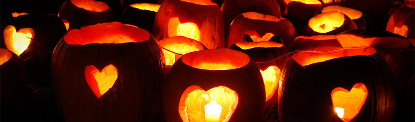 Three pumpkins lined up with each other with hearts cut out.