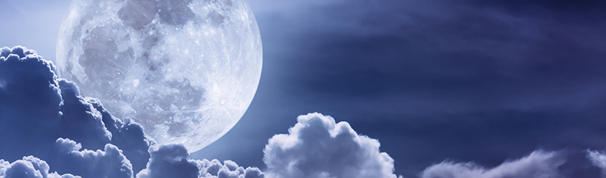 A full moon is above some clouds. The image has a blue tone to it.