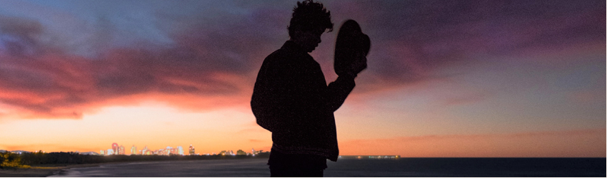 Man with a hat stands in front of a sunset.