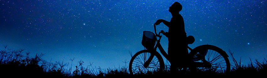 A man on a bike looks up at the stars.