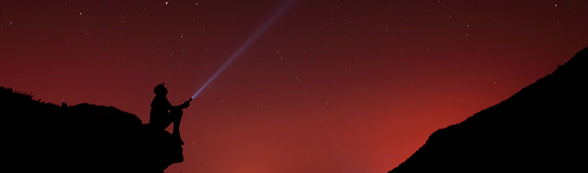 A person on a cliff shining a flashlight out towards the red sky. The stars shine brightly.