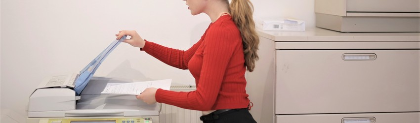 A person making a photocopy in an office.