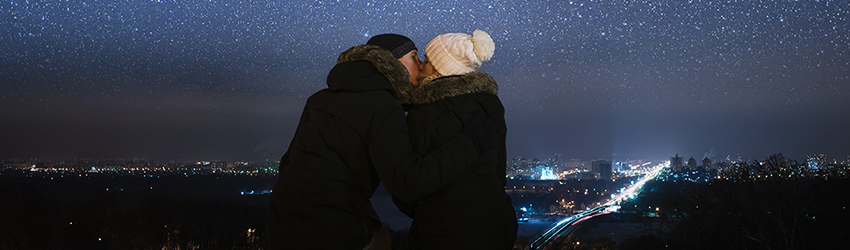 A couple kissing on a cold winter night. An asteroid falls in the background.