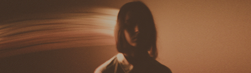 A blurry woman standing in a sepia tone room.