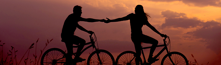 Two people are riding bikes and their silhouettes are visible on a sunset sky.