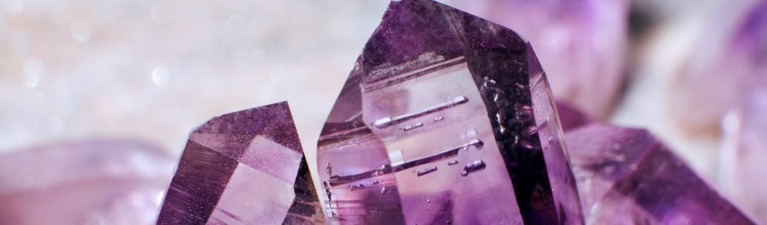 Purple amethyst crystal points resting next to each other on a purple background.