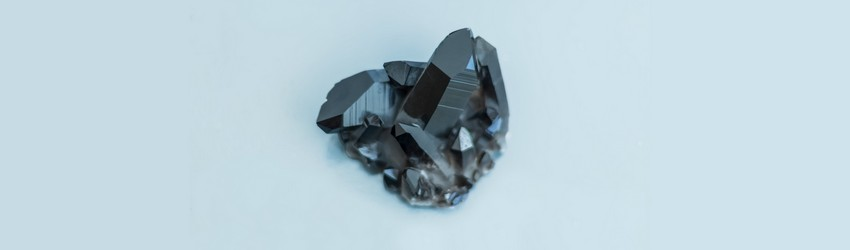 A black hematite crystal on a blue background.