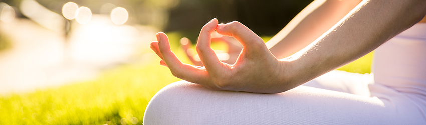 A person sits meditating in the sun. They are healing their chakra through self-care.