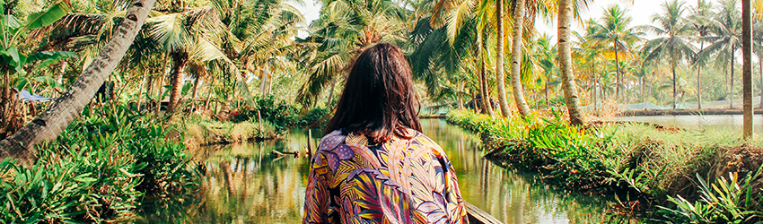 Woman entering a rain forest scene. She is wearing a bold shirt filled with blue, red, and purple swirled. She is in a boat and is looking towards the horizon.